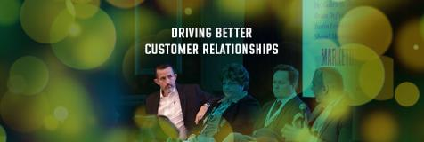 "Hans Kaspersetz leading a conference panel and a banner stating ""Driving Better Customer Relationships"""