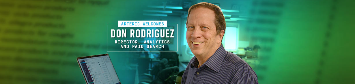 "Don Rodriguez in front of a laptop computer and adjacent to a banner that reads, ""Arteric welcomes Don Rodriguez, Director, Analytics and Paid Search"""
