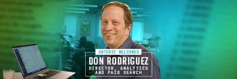 "on Rodriguez in front of a laptop computer and adjacent to a banner that reads, ""Arteric welcomes Don Rodriguez, Director, Analytics and Paid Search"""